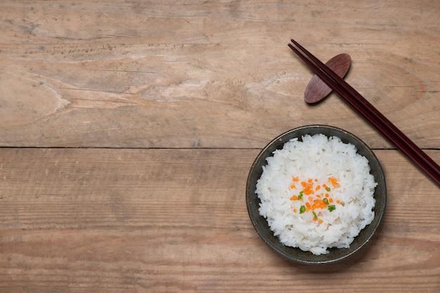 Perto de arroz cozido em madeira em uma tigela na mesa de madeira