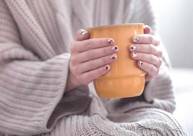 Perto de belas mãos femininas segurando uma xícara grande de cappuccino, café e flores