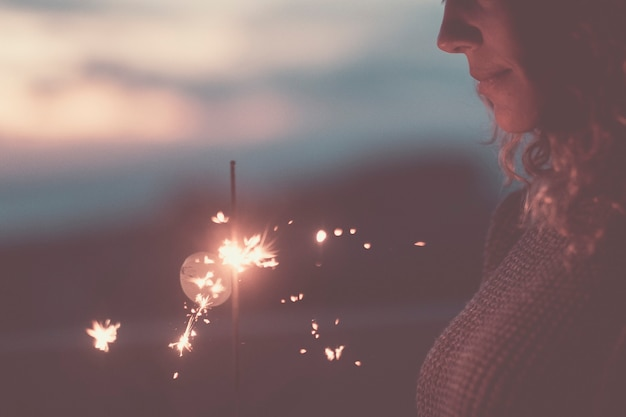 Perto de brilhantes fogos de artifício e lindo rosto de mulher caucasiana