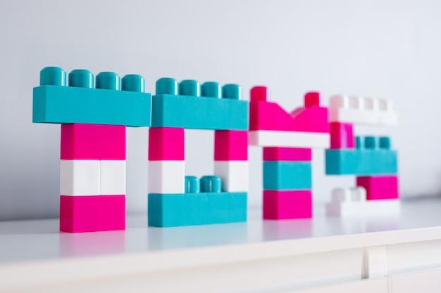 Perto de brinquedos de palavras dobrados de construtor de brinquedo colorido