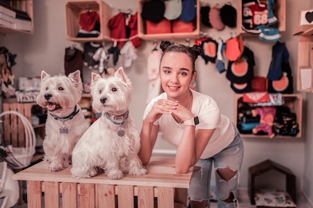 Perto de cachorros fofos. mulher fofa de olhos escuros usando uma camiseta branca perto de cachorrinhos fofos