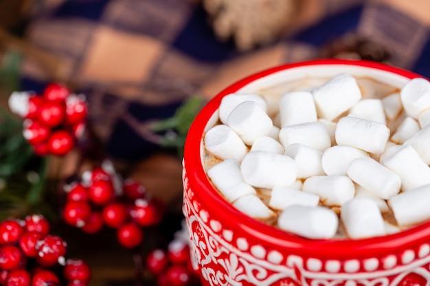 Perto de caneca vermelha com cacau e marshmallows, natal e ano novo