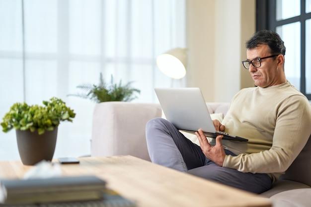 Perto de casa latina bonito empresário de meia idade em óculos usando laptop enquanto trabalhava