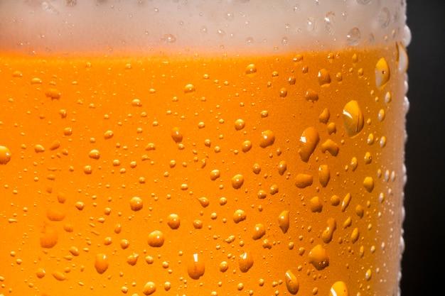 Perto de cerveja gelada com gotas e bolhas