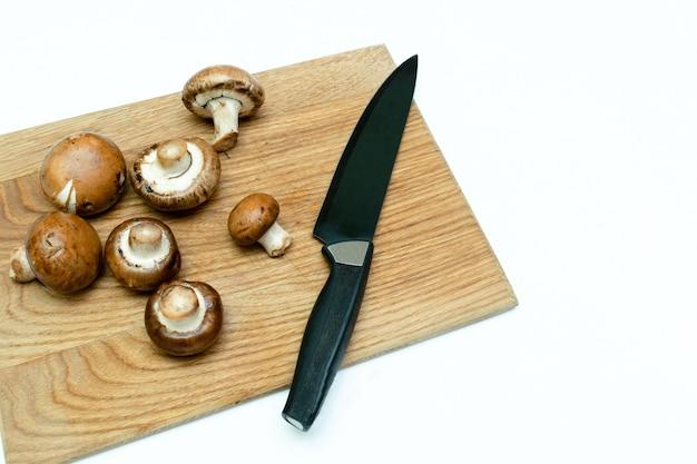 Perto de cogumelos frescos e faca em uma tábua de madeira em uma cozinha em casa.
