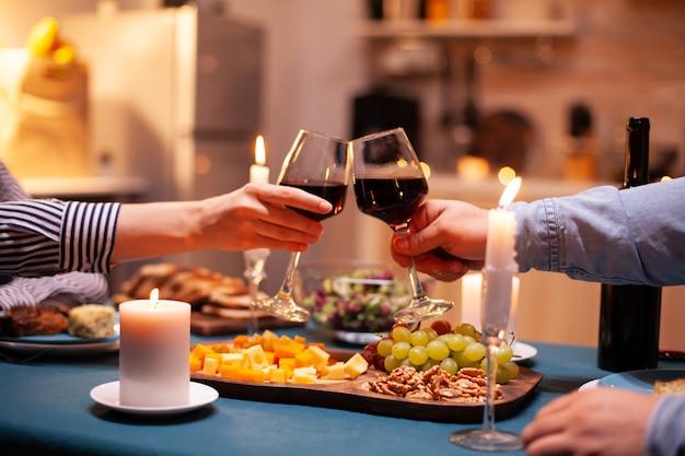 Perto de copos tilintando com vinho durante o jantar romântico, jantar celebrando o relacionamento. casal jovem alegre e feliz jantando juntos na cozinha aconchegante, aproveitando a refeição e comemorando o aniversário de casamento