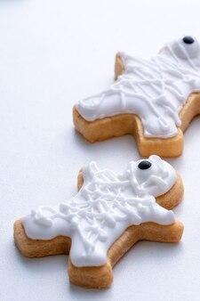Perto de decorar biscoitos de gengibre bonitos de halloween com saco de cobertura de creme de confeiteiro de glacê.