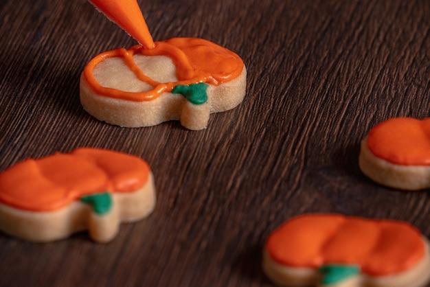Perto de decorar biscoitos de gengibre de abóbora de halloween fofos com saco de cobertura de creme de confeiteiro de glacê.
