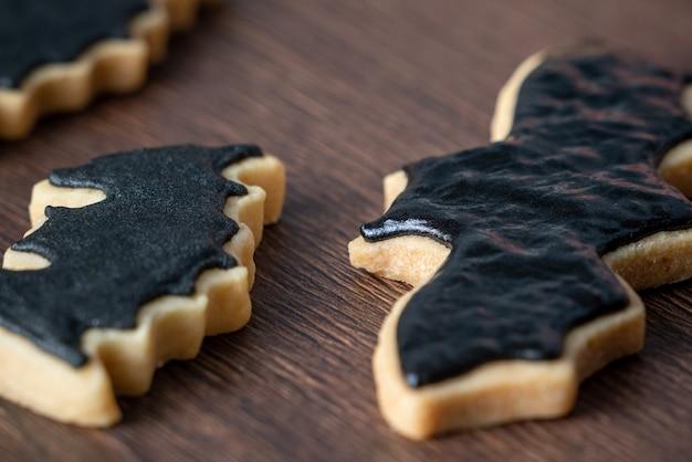 Perto de decorar biscoitos de gengibre de morcego de halloween fofos com saco de cobertura de creme de confeiteiro de glacê.