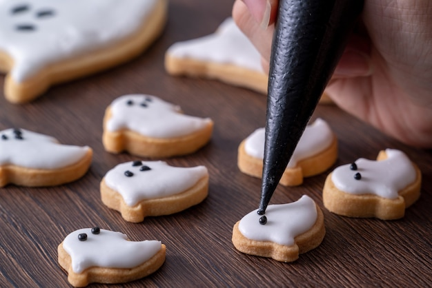Perto de decorar biscoitos de gengibre fantasma de halloween fofos com saco de cobertura de creme de confeiteiro de glacê.