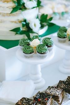Perto de deliciosos bolos de geleia verdes em bandejas de madeira na mesa no buffet de casamento doce. barra de chocolate. variedade de bela porção de doces.