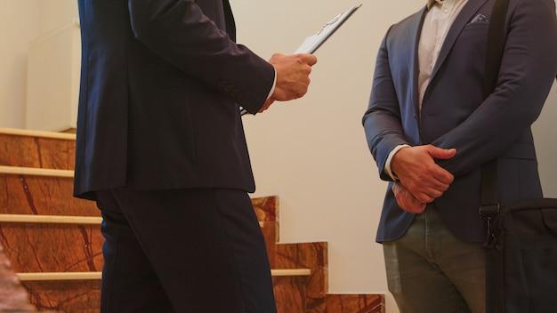 Perto de dois homens de negócios de terno, apertando as mãos em pé na escada da empresa, conversando. grupo de empresários profissionais de sucesso trabalhando no moderno local de trabalho financeiro.