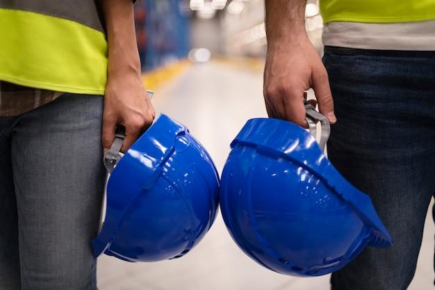 Perto de dois trabalhadores industriais irreconhecíveis segurando capacetes de proteção de capacete
