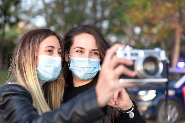 Perto de duas garotas usando máscaras com uma câmera analógica nas mãos.