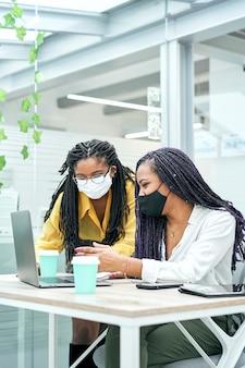 Perto de duas jovens empresárias usando máscara enquanto trabalhava no laptop