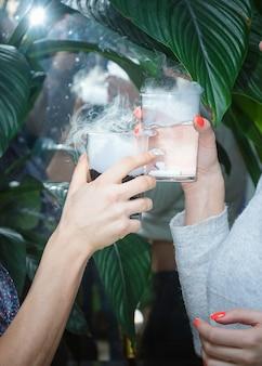 Perto de duas mãos segurando coquetéis de gelo seco na festa.