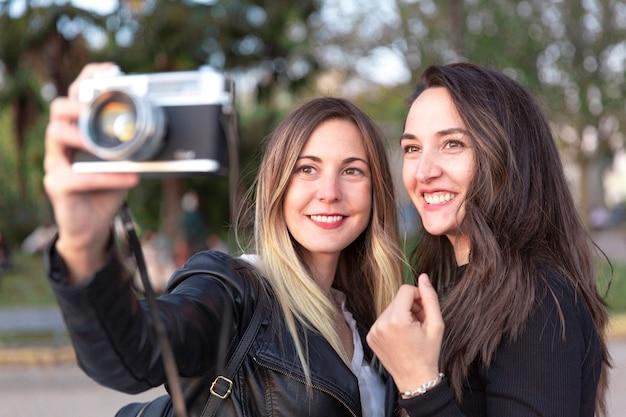 Perto de duas mulheres sorridentes com uma câmera analógica nas mãos.