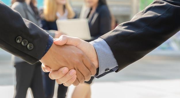 Perto de empresários apertando as mãos. dois empresários encontrando-se ao ar livre com empresários