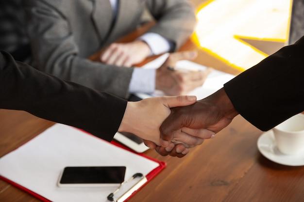 Perto de empresários apertando as mãos na sala de conferências