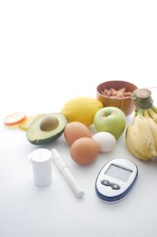 Perto de ferramentas de medição para diabéticos e frutas frescas em fundo branco