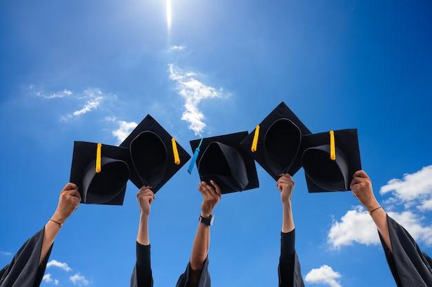 Perto de graduados segurando chapéus nas mãos
