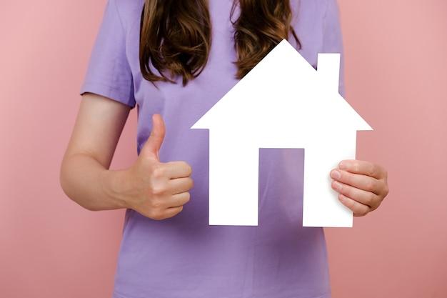 Perto de irreconhecível jovem apontando no modelo de casa de papel branco e faz como gesto, aprovação de casa imobiliária, isolada no fundo rosa no estúdio. conceito de serviço social sobre casa