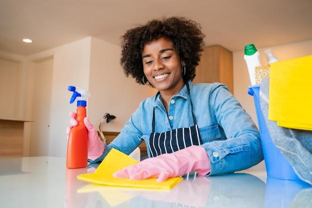 Perto de jovem afro, limpando a nova casa. conceito de arrumação e limpeza.