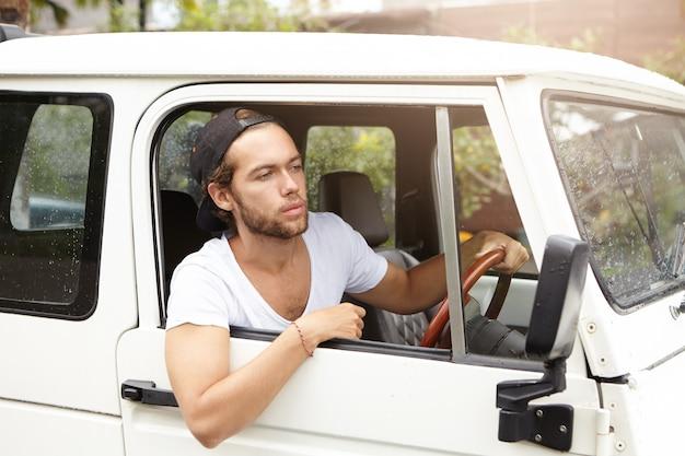 Perto de jovem atraente com barba, sentado em seu veículo branco em busca de extrema durante a viagem de safari. macho em snapback dirigindo na estrada rural