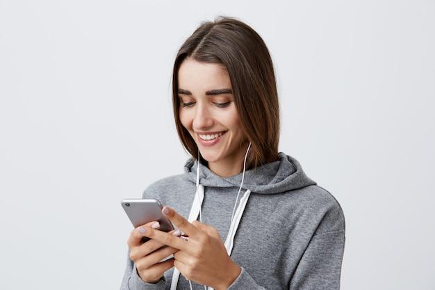 Perto de jovem atraente feliz caucasiana atraente com longos cabelos escuros com capuz cinza rindo, olhando o vídeo engraçado da festa no telefone, ouvindo a música favorita com fones de ouvido.