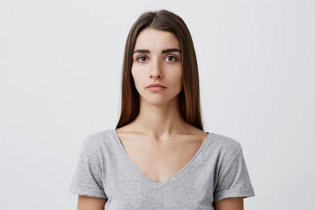 Perto de jovem bonita e encantadora garota caucasiana com cabelos castanhos compridos em t-shirt cinza com expressão séria. foto de mulher ficando para passaporte.