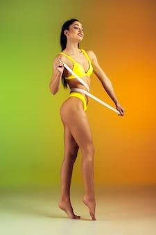 Perto de jovem em forma e mulher esportiva com medidor em elegante maiô amarelo em parede gradiente, corpo perfeito pronto para o verão