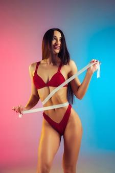 Perto de jovem em forma e mulher esportiva com medidor em elegante maiô vermelho em parede gradiente, corpo perfeito pronto para o verão