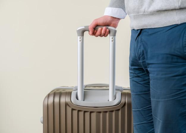 Perto de jovem homem de negócios com mala de bagagem no aeroporto