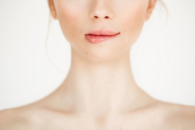 Perto de jovem linda com a pele limpa, saudável, morder o lábio. copie o espaço. cosmetologia e spa