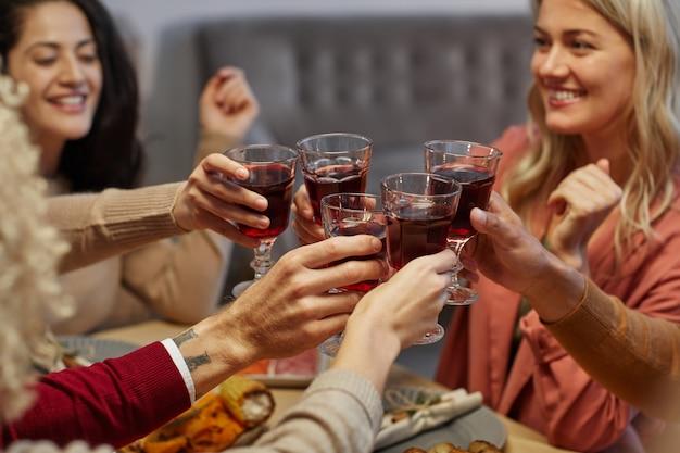 Perto de jovens alegres batendo copos enquanto estão sentados à mesa juntos e desfrutando do jantar de ação de graças com amigos e familiares,
