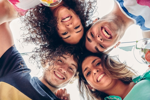 Perto de jovens felizes com suas cabeças juntas, se divertindo em uma festa de verão. conceito de estilo de vida dos jovens. veja de baixo. Foto Premium