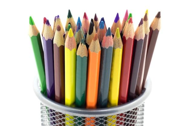 Perto de lápis de cor em um suporte de metal em um fundo branco e isolado