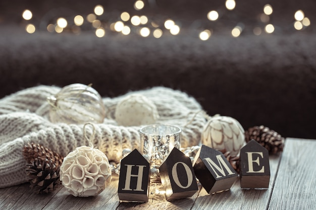 Perto de letras de madeira fazem a palavra casa, detalhes de decoração de natal em fundo desfocado com bokeh.