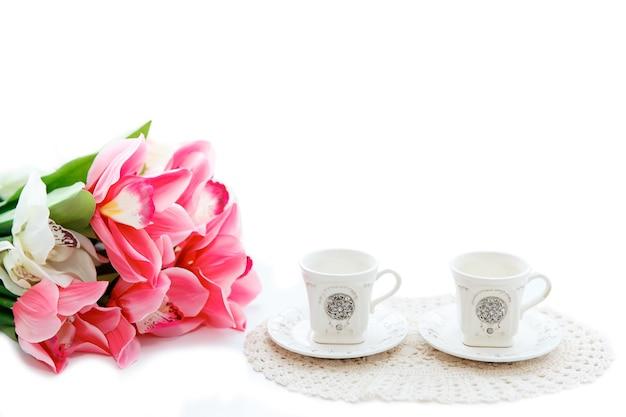 Perto de lindas tulipas vermelhas em um vaso e duas xícaras em um fundo branco. copyspace.