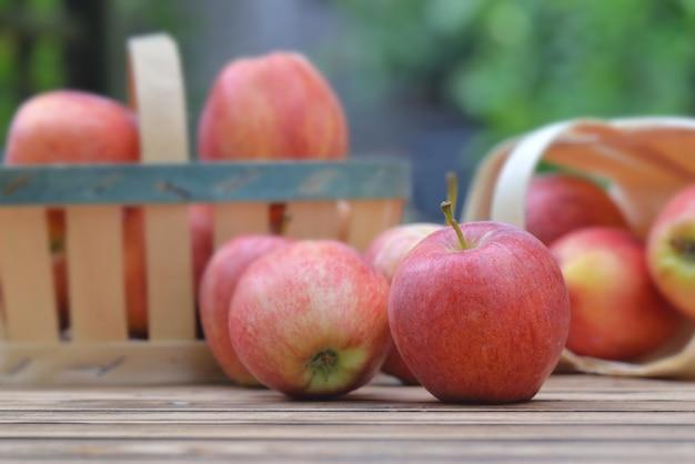 Perto de maçãs vermelhas em uma pequena cesta em uma mesa de madeira no jardim sobre fundo verde