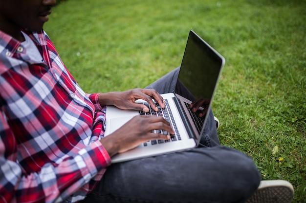 Perto de mãos afro-americanas digitando no laptop na grama verde