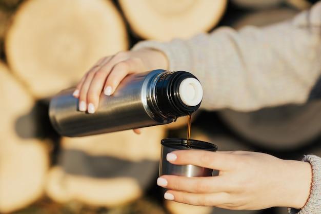 Perto de mãos femininas servindo uma bebida quente em uma caneca térmica