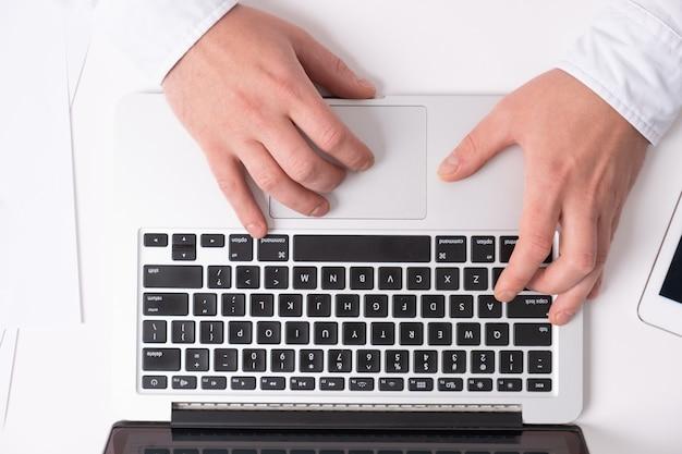 Perto de mãos masculinas digitando no teclado do laptop enquanto trabalha na mesa branca