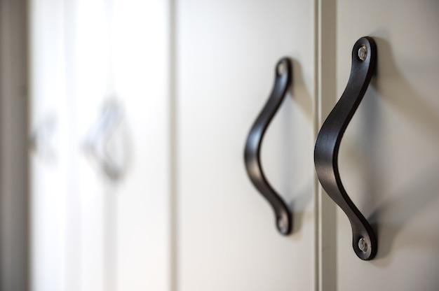 Perto de móveis minimalistas brancos com puxadores pretos, armário de cozinha, detalhes.