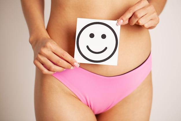 Perto de mulher com figura esbelta, segurando perto de cartão de barriga com sorriso sorrindo