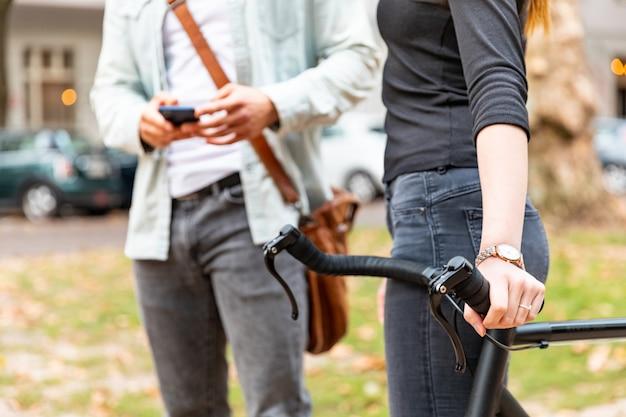 Perto de mulher com uma bicicleta e homem com telefone