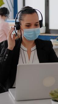 Perto de mulher de negócios com máscara facial usando fone de ouvido, falando no microfone enquanto digita estatísticas de marketing no computador portátil. freelancer sentado à mesa no escritório durante a pandemia de covid19