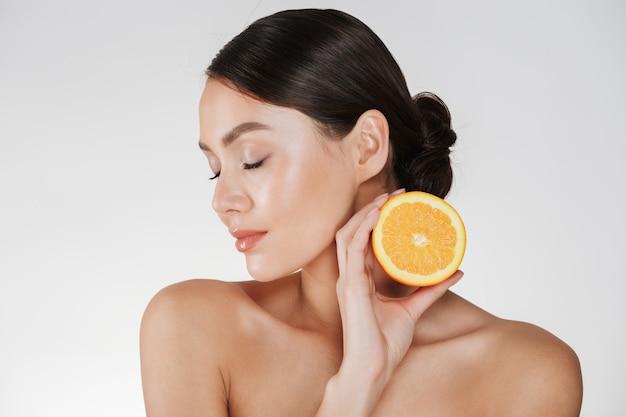 Perto de mulher encantadora, com pele fresca macia, segurando a laranja suculenta, tendo a desintoxicação isolada sobre o branco