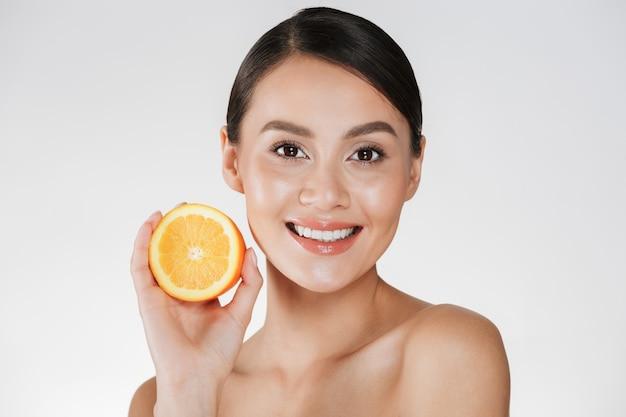 Perto de mulher satisfeita com a pele fresca saudável, segurando a laranja suculenta e sorrindo, isolado sobre o branco