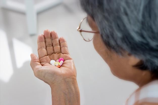 Perto de mulher sênior com comprimidos e copo de água em casa, tomar remédio.